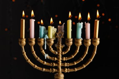 Glowing candles in menorah on black background with bokeh lights on Hanukkah stock vector