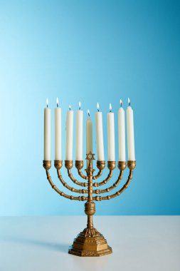 burning candles in menorah on blue background