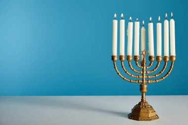 burning candles in menorah isolated on blue