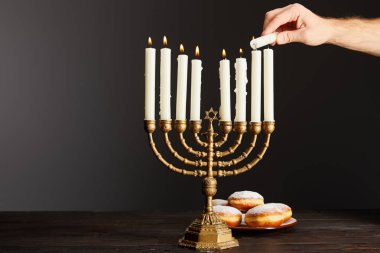 Cropped view of man lighting up candles in menorah near doughnuts on black background on Hanukkah stock vector