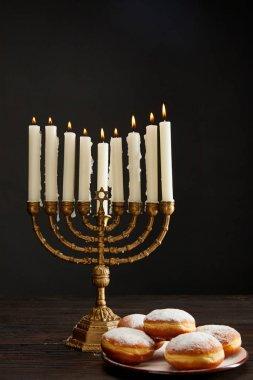 Delicious doughnuts near burning candles in menorah on Hanukkah isolated on black stock vector