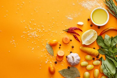 Top view of fresh vegetables with herbs and spices on orange background