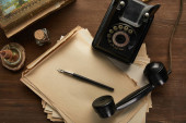 top view of vintage paper, painting, fountain pen, candle and dial phone on wooden table