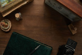 top view of vintage camera, photo album, painting, fountain pen, stamp and clock on wooden table