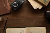 horní pohled na vinobraní fotoaparátu, fotoalbum, malba, plnicí pero na dřevěném stole