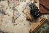 horní pohled na vinobraní fotoaparátu, poznámkový blok s plnicím perem, razítkem a malbou na pozadí mapy