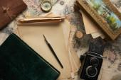 horní pohled na vinobraní fotoaparát, kompas, plnicí pero, fotoalbum, papír a malba na pozadí mapy