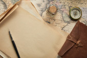 top view of vintage blank paper with fountain pen near compass and leather notepad on map background