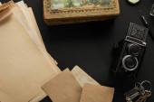 Draufsicht auf alte Kamera, Papier, Malerei, Füllfederhalter, Tasten auf schwarzem Hintergrund