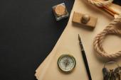 horní pohled na vinobraní papíru, lana, kompas, razítko, klíče a plnicí pero na černém pozadí
