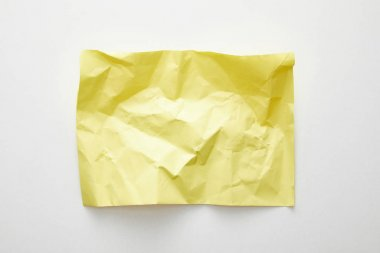 top view of empty crumpled yellow paper on white background