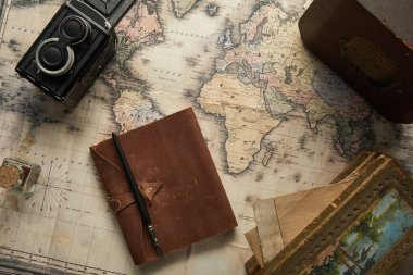 top view of vintage camera, notepad with fountain pen, radio and painting on map background