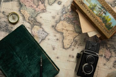 top view of vintage camera, compass, fountain pen, photo album and painting on map background