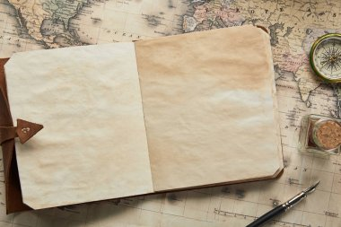 top view of vintage blank notebook with fountain pen near compass on map background