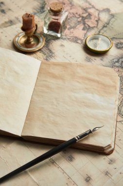 selective focus of vintage blank notebook with fountain pen near compass and candle on map background