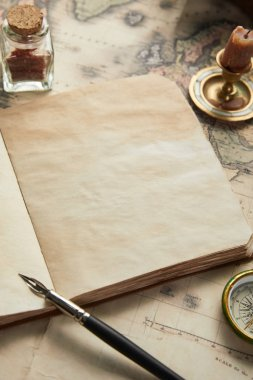 vintage blank notebook with fountain pen near compass and candle on map background