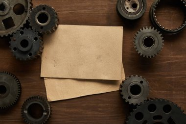 top view of vintage paper and gears on wooden table