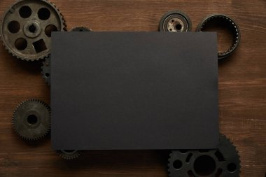 top view of vintage black paper and gears on wooden table