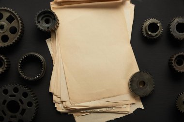 top view of aged gears and vintage blank paper on black surface
