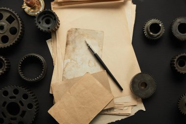 top view of aged gears and vintage blank paper with fountain pen on black surface