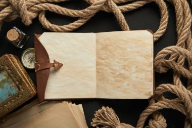 top view of vintage notebook, rope, compass and painting on black background