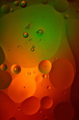 Photo abstract background from mixed water and oil bubbles in green and red color