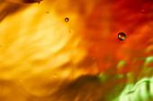 Krásné abstraktní oranžové, červené a zelené barvy pozadí ze smíšené vody a oleje