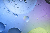 abstract background from mixed water and oil in blue, purple and green color