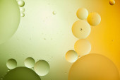 creative abstract background from mixed water and oil in green and orange color