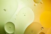 abstraktní pozadí ze smíšené vody a oleje v zelené a oranžové barvě