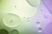 abstraktní pozadí ze smíšené vody a oleje ve světle zelené a fialové barvě