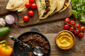 Top view of delicious tacos with minced meat on cutting board and ingredients on wooden background