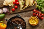 Top view ízletes taco darált hús vágódeszka és összetevők fa háttér