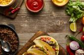 Blick von oben auf leckere Tacos mit Hackfleisch und frischen Zutaten auf Holzoberfläche