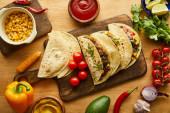 Horní pohled na tacos s masem a čerstvými ingrediencemi na dřevěném stole