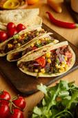 Fotografie Lahodné tacos se zralou zeleninou a zelení na dřevěném stole