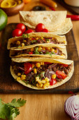 Fresh tacos with organic ingredients on wooden background