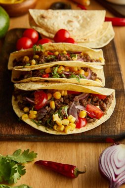 Tacos with minced meat on cutting board with parsley and vegetables on wooden table