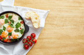 pohled shora na smažená vejce v blízkosti chleba a rajčata na ubrousku na dřevěném stole