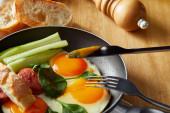 smažená vejce na pánvi se zeleninou a klobásou u vidličky, nůž, chléb u dřevěného stolu