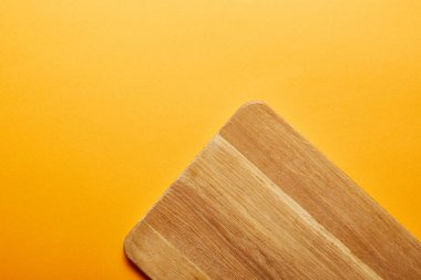 Top view of wooden cutting board on orange background stock vector