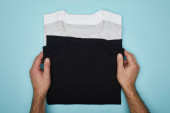 cropped view of man touching blank basic black, white and grey t-shirts isolated on blue