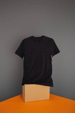 Basic black t-shirt on cube on grey and orange background stock vector