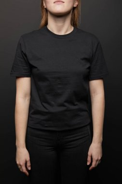 Cropped view of woman in blank basic black t-shirt on black background stock vector