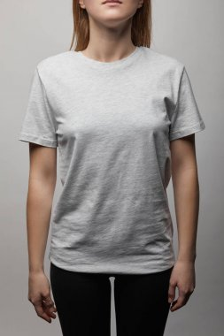 Cropped view of woman in blank basic grey t-shirt on grey background stock vector