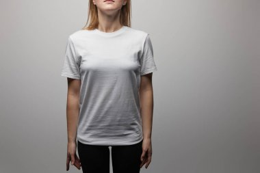 Cropped view of woman in blank basic white t-shirt on grey background stock vector