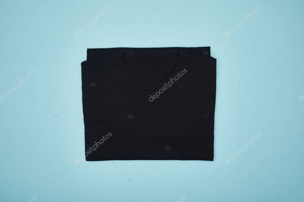 Top view of blank basic black t-shirt isolated on blue stock vector