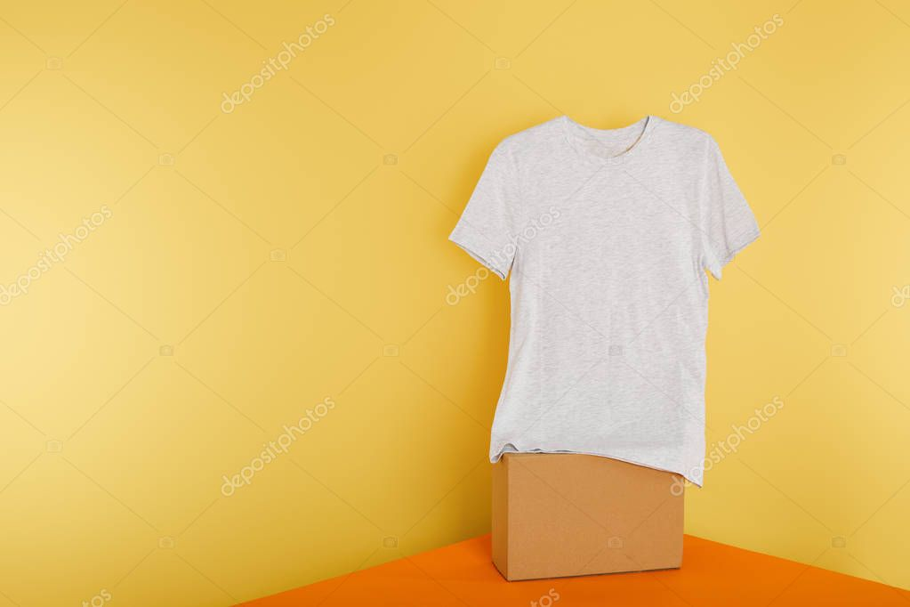 Basic grey t-shirt on cube on yellow background stock vector
