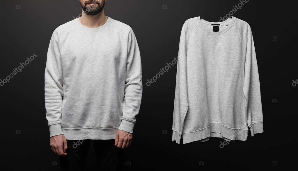 Cropped view of bearded man near blank basic grey sweatshirt isolated on black stock vector