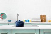 messa a fuoco selettiva degli interni moderni della cucina bianca e turchese con pentola sul piano cottura a induzione elettrica
